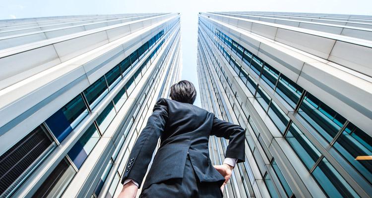 高層ビルを見上げるビジネスマン,ローアングル